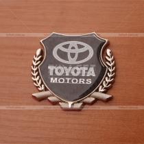 Эмблема Тойота на карбоновом фоне с хромированным гербом