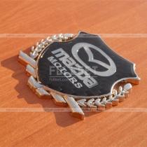 Эмблема герб Mazda на карбоновом фоне (размер: 6,5 см на 5,5 см)
